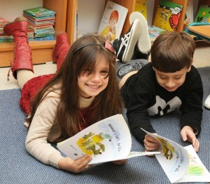 photo - Children enjoying their books about Soumsoum the Mouse as part of the Maktabat al-Fanoos program, which fosters a love of reading