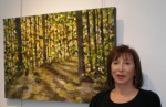 photo - Melanie Fogell with one of her paintings