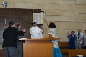 photo - Beth Israel executive director Shannon Etkin lifts the Torah during the dedication of the new building