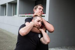 photo - Krav maga instructor Jonathan Fader prepares to get out of a choke hold