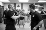 photo - Jonathan Fader, left, and his business partner Borhan Jiang show a class at Urban Tactics Krav Maga how to disarm an attacker who has a knife
