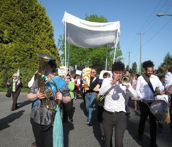 photo - During the parade, led by the Balkan Shmalkan band, the Torah was carried by many different congregation members. In this photo, Henry Grayman is holding it.