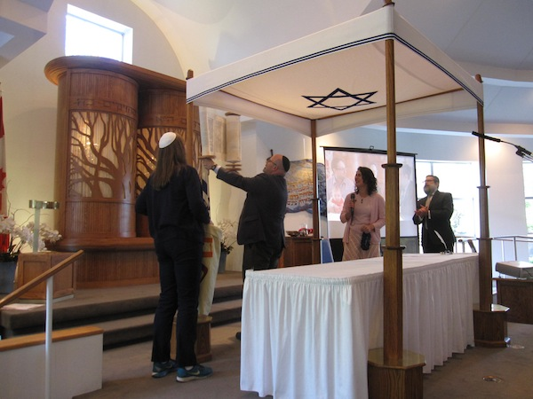 photo - Rabbi Dan Moskovitz raises the newly completed Torah as, left to right, Cantor Naomi Taussig, Rabbi Carey Brown and Rabbi Moshe Druin look on.