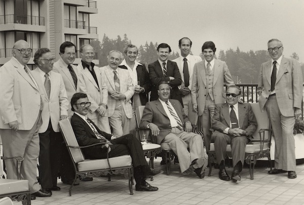 photo - Group of men on an outdoor patio, Vancouver, Aug. 30, 1979. Morris Wosk is standing, fifth from the left, and Joe Cohen is seated in the centre