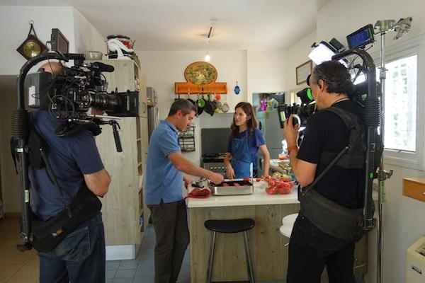 photo - Michael Solomonov being filmed in the kitchen of Krav Sakinim (Israel's Iron Chef) judge Ruthie Rousso