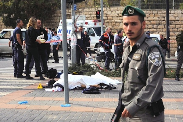photo - A border policeman walks past the covered body of a victim of the terror attack near the Jerusalem light rail in November 2014