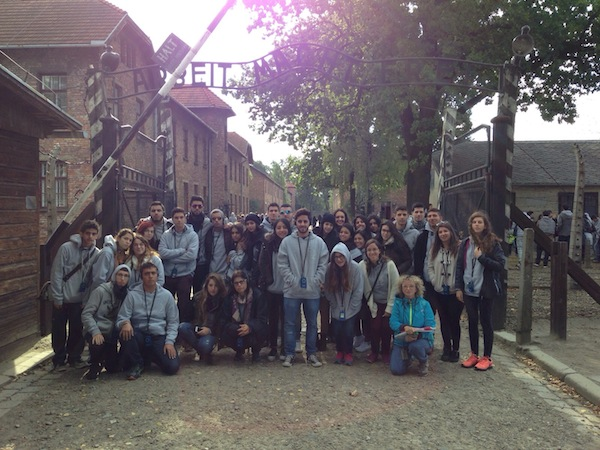 "photo - The whole group at Auschwitz concentration camp under the infamous sign, ""Arbeit Macht Frei,"" ""Work Makes You Free."""