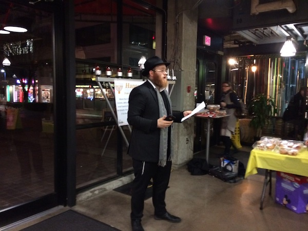 photo - Chabad of North Shore Rabbi Mendy Mochkin speaks at the first-ever menorah lighting at Lonsdale Quay