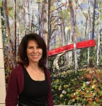 photo - Lori Goldberg in front of one of her paintings