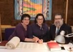 photo - Nomi Fenson, left, and Debby Fenson help complete Congregation Beth Israel's new sefer Torah with sofer Rabbi Moshe Druin
