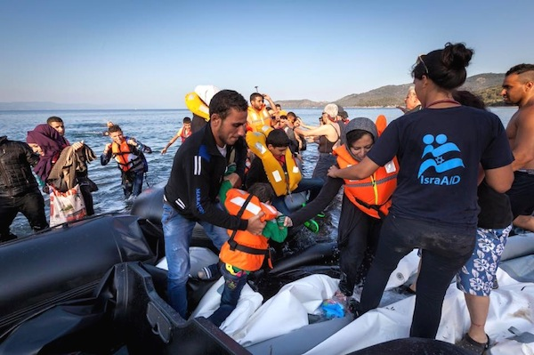 photo - Medical and rescue teams from IsraAID attend to Syrian refugees who have just landed in a rubber boat on the Greek island of Lesbos after the perilous crossing from Turkey