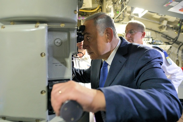 photo - Prime Minister Binyamin Netanyahu looks through the periscope of the latest submarine to be delivered to the Israeli navy by the German government