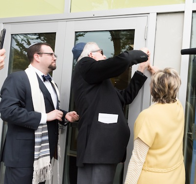 photo - Vancouver Talmud Torah Rabbi Marc Kasten looks on as Gordon and Leslie Diamond, lead donors, affix a mezuzah to the school