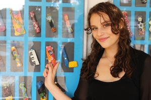 photo - Keren Katz, class of 2016 graduate and one of the Hallelujah Singers, points to the mezuzah she made as part of a class project to leave a legacy to the school. The project, facilitated by VTT parent and artist Dina Sacks, will continue with future graduating classes to fill the Glassman Gallery with original, student-created mezuzot containing a special Jewish-themed wish