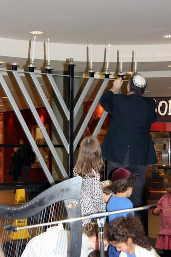 photo - Cantor Yaakov Orzech lights the menorah