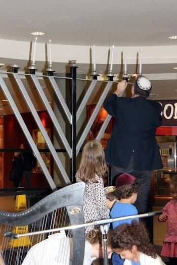 photo - Cantor Yaakov Orzech lights the menorah