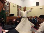 photo - David Coskun dances as Seemi Ghazi speaks