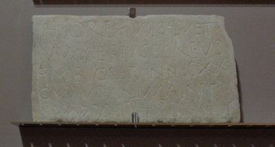 photo - The tombstone for the young Jewish Numerius, written in both Latin and Hebrew, which can be seen at the National Archeology Museum in Naples. Note the menorah in the middle of the bottom line