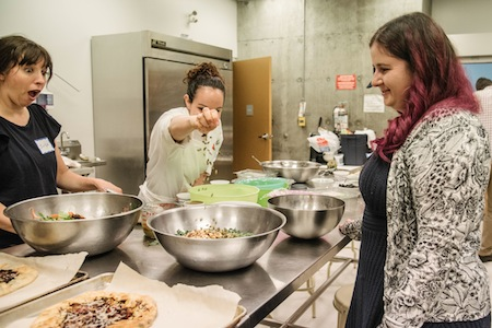 photo - Chef Lior Ben-Yehuda puts the finishing touches on a salad as Erika Balcombe, left, and JMABC archivist Alysa Routtenberg look on