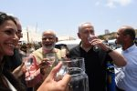 photo - On July 10, at Givat Olga, Indian Prime Minister Narendra Modi, centre-left, and Israeli Prime Minister Binyamin Netanyahu sample water that has just been purified to the World Health Organization standard in the Galmobile.