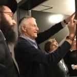 photo - Gordon Diamond hangs the mezuzah at the opening of the Diamond Residences on Oct. 17, as Rabbi Levi Varnai looks on