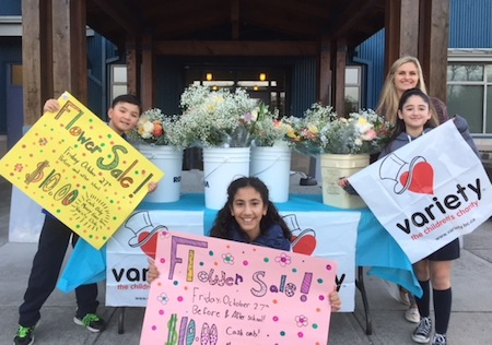 photo - Among other initiatives, RJDS students sold flowers to raise money for Variety. Pictured here are, left to right, Jonathan Estok, Noa Ben-David and Hannah Karasently-Saltoun with teacher Dara Nelson (in the back)