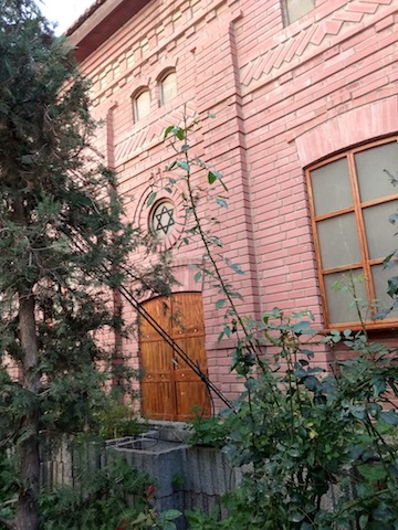 photo - A garden lies to the side of the ohel, and the façade of the adjoining building recalls the original Ger yeshivah in Góra Kalwaria, Poland