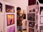 photo - From generation to generation: A Peretz Centre reunion attendee pauses to send a text while walking through an exhibit of archival photos
