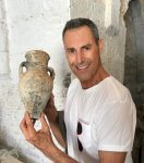 photo - Uri Geller holds a water or oil jug that was found during the construction of a new museum dedicated to his activities