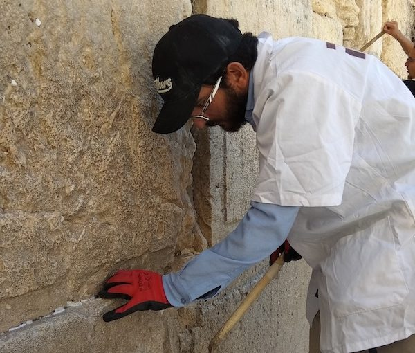 photo - Crews from the office of the Rabbi of the Western Wall remove tens of thousands of written prayers from the Western Wall