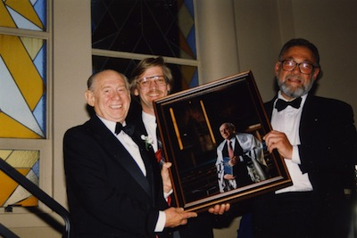 photo - Cantor Murray Nixon, left, and Rabbi Wilfred Solomon, right, hold a framed photo of Nixon taken by Don McGregor, middle, at Beth Israel, circa 1995