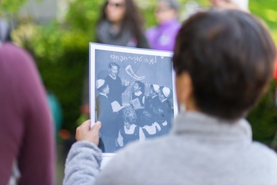 photo - A tour participant holds up a picture from the Talmud Torah Grade 4 class, circa 1965; Gita Kron, teacher