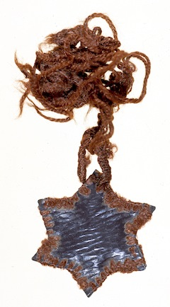 photo - Margit (Manci) Rubenstein made this Star of David necklace from material taken from the lining of her shoes and shoelaces while imprisoned in Auschwitz (1944)