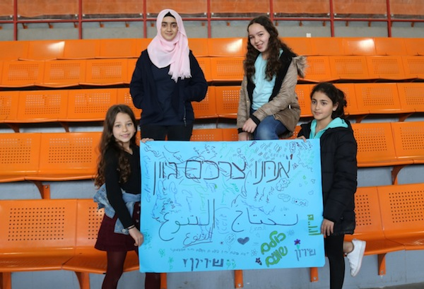 "photo - Children in the Arab village of Kalansua with a poster stating, ""We need diversity"" and ""We are all equal"" in Hebrew and Arabic"