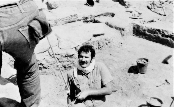 photo - In the summer of 1969, the author worked on an archeological dig. Here, he passes up a bucket of dirt for disposal. In the background, partially covered with a rock slab, is a Bedouin grave dating to the Middle Ages