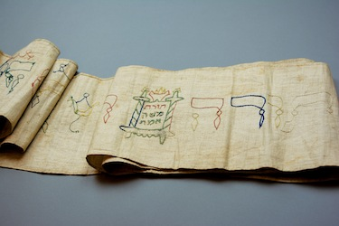 photo - Dr. Michael Hayden, the grandson of Max and Gertrud Hahn, discovered in the 1980s that this Torah binder was in the possession of the City Museum in Göttingen. The piece of cloth was used to swaddle his great-grandfather Raphael Hahn for his brit milah (circumcision ceremony) in 1831. With the help of Göttingen's mayor, Hayden organized for the Torah binder to be returned to his family
