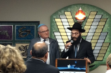 photo - Rabbi Levi Varnai speaks as Keith Liedtke looks on