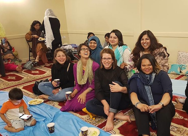 photo - Members of Sisterhood of Salaam Shalom enjoy a Ramadan Iftar dinner together at a local mosque. Naz Qureshi is at top right and Rabbi Gila Caine is seated in the front row, second from the right. This photo was taken before the COVID-19 crisis