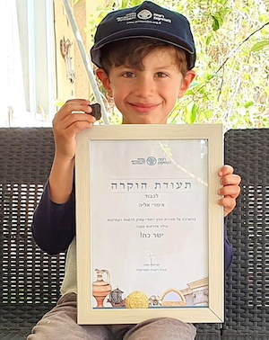 photo - Imri Elya, 6, from Kibbutz Nirim, near the Gaza Strip, holds his certificate of good citizenship and the tablet he found