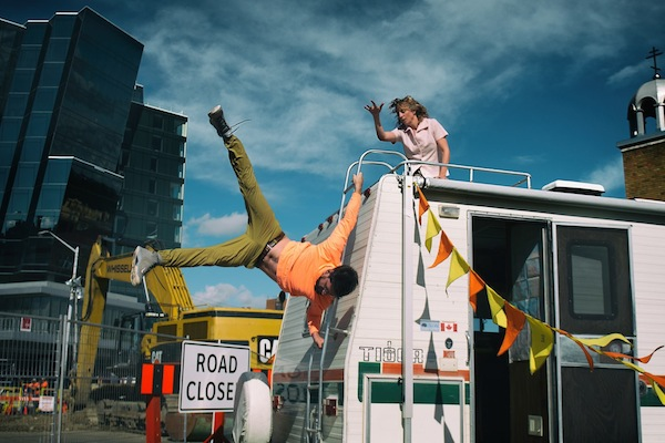 photo - Ben Gorodetsky hangs on to an RV's ladder in There Yet by Edmonton's Mile Zero Dance