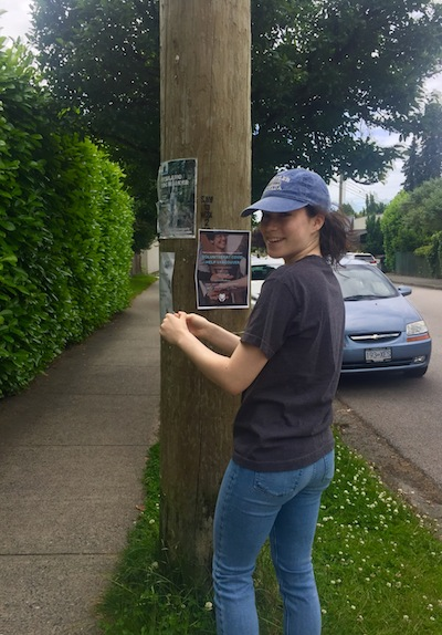 photo - COVIDhelp Vancouver's director of outreach communication, Rebecca Baron, tapes a poster to an electricity pole to spread the word about the group's services