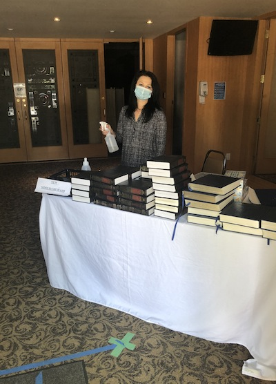 photo - Office administrator Anna Herman is among those who sanitize the prayer books for congregants to use at services
